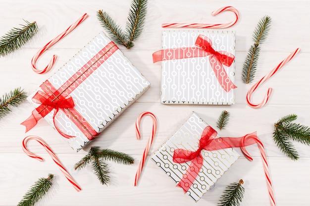 Fond de noël cadeaux, branches de sapin, décorations rouges sur fond en bois blanc. lay plat, vue de dessus