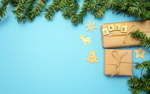 Fond de noël avec des cadeaux en papier craft et un arbre de noël sur fond bleu. réductions pour noël.