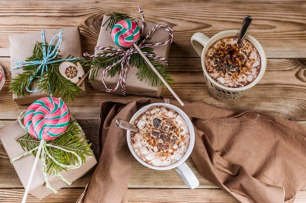 Fond de noël café avec guimauves, cadeaux, branches et sucettes sur bois