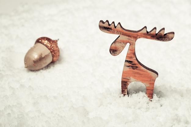 Fond de noël avec des cerfs de noël à la main sur fond de neige blanche