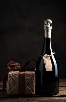 Fond de noël avec champagne et cadeau sur fond marron