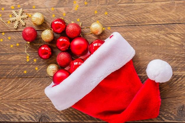 Fond de noël. chapeau de père noël plein de boules rouges et or sur fond en bois.