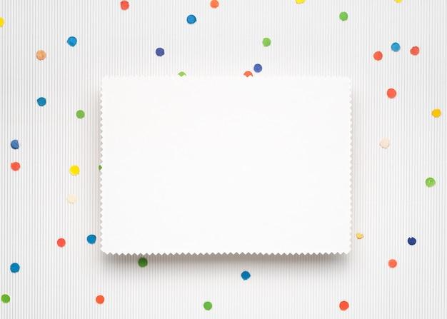 Fond de noël clair avec des confettis festifs. feuille de papier blanc avec espace de copie pour le texte