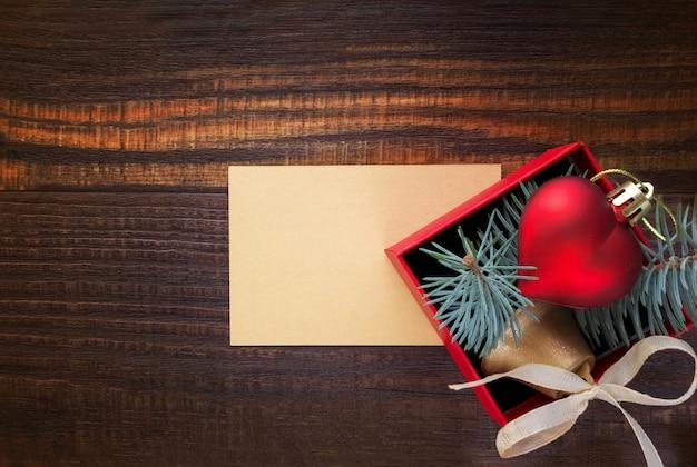 Fond de noël: coffret rouge avec un jouet de noël en forme de coeur, une cloche d'or, des branches de sapin et une carte pour le texte de félicitations
