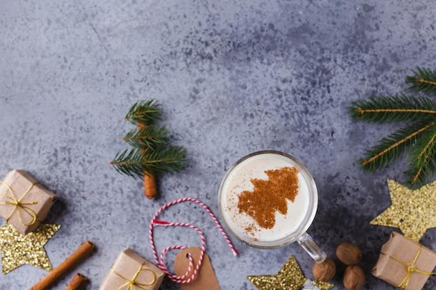 Fond de noël avec, coffrets cadeaux, décor festif, sapin, bâtons de cannelle, boisson chaude au lait de poule.