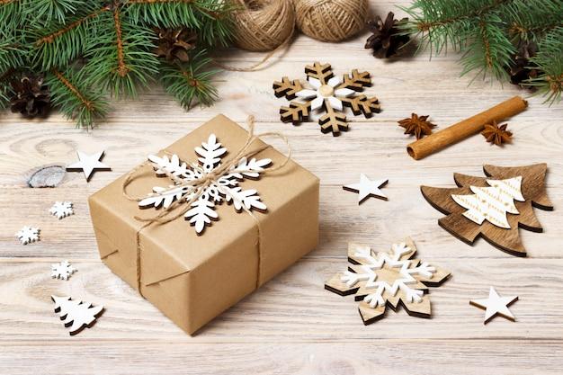 Fond de noël avec des coffrets cadeaux enveloppés dans du papier kraft, des branches de sapin, des pommes de pin, des bâtons de cannelle et des anis étoilés sur fond en bois blanc