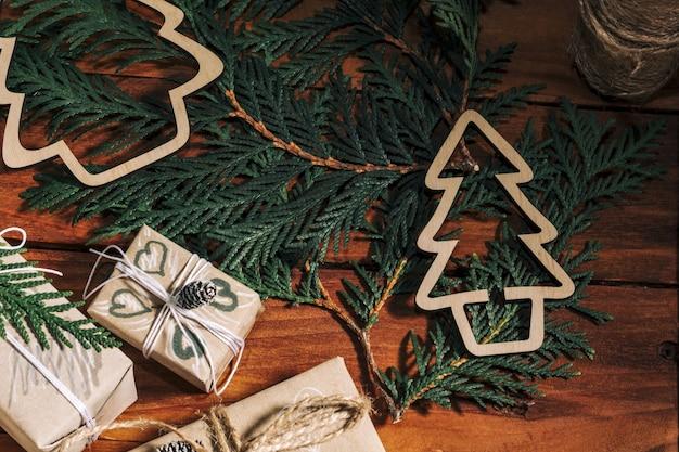 Fond de noël avec des coffrets cadeaux faits à la main, des points de corde et des décorations avec des pommes de pin et des brindilles sur fond en bois. préparation pour les vacances. fait main. mise au point sélective.