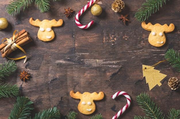 Fond de noël. composition de noël avec des branches de sapin, cadeaux, bonbons, biscuits, cannelle sur fond de bois sombre