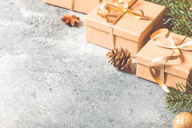 Fond de noël. composition de noël avec des branches de sapin, cadeaux, bonbons, cannelle sur fond de béton clair
