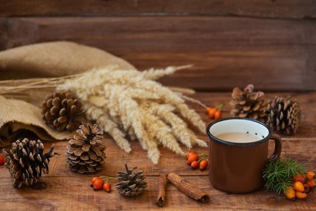 Fond de noël dans un style rustique. une tasse en métal avec du thé au lait chaud se dresse sur une nappe, sur une surface en bois parmi des pommes de pin, des branches d'épinette, des épillets de blé et d'églantier. espace de copie, mise à plat