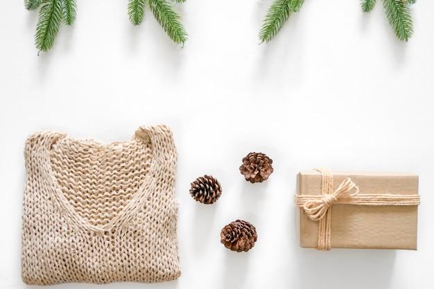 Fond de noël avec décoration, cadeau, pommes de pin, branches, bulle d'or et pull à tricoter et espace de copie