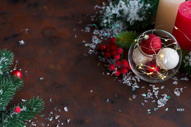 Fond de noël avec décoration de fête, bougies, lumière et boules en pot.