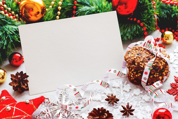 Fond de noël avec des décorations, des biscuits, des pommes de pin et du papier clair pour votre texte.
