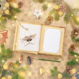 Fond de noël avec décorations et cahier sur papier kraft dans un style rustique. avec des lumières bokeh. flatlay.