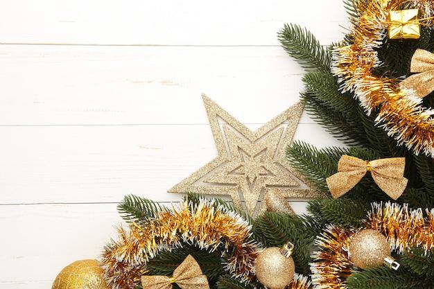 Fond de noël avec des décorations en or et coffret cadeau sur planche de bois blanche. vue de dessus.
