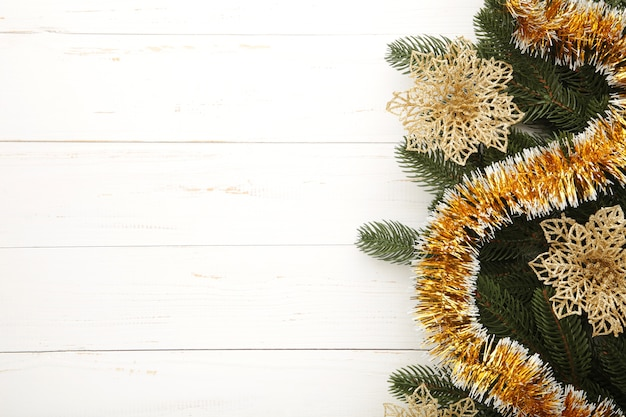 Fond de noël avec des décorations en or sur fond en bois blanc. vue de dessus.