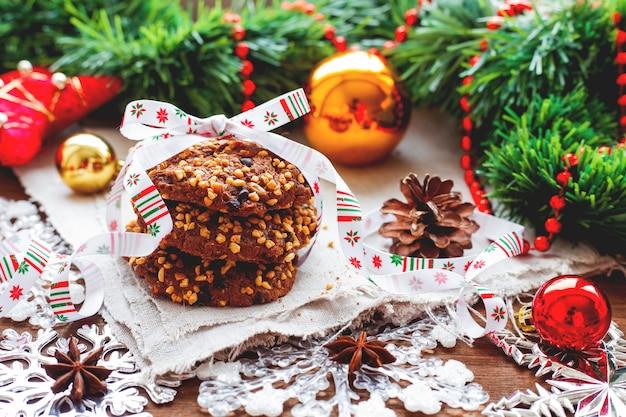 Fond de noël avec des décorations, des pommes de pin et une pile de délicieux biscuits avec ruban de vacances.