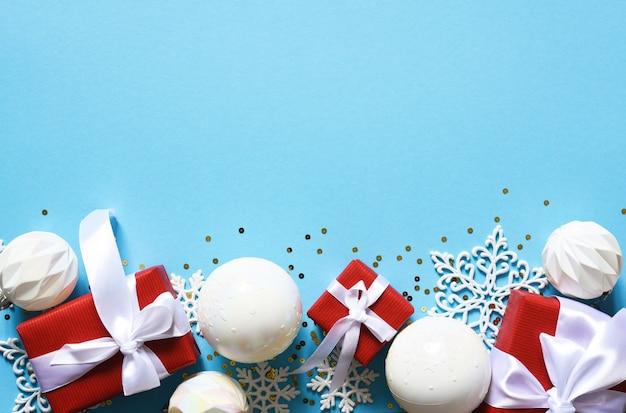Fond de noël délicat bleu avec des boules blanches. lumières de bokeh. décor du nouvel an. cadeaux.