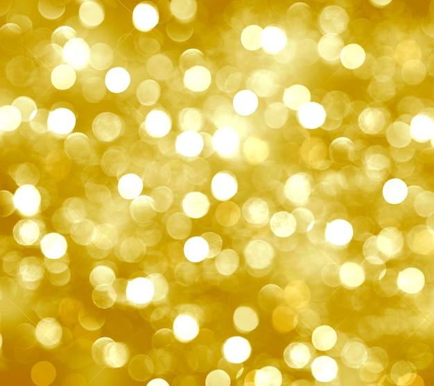 Fond de noël doré avec des cercles de bokeh flou jaune brillant