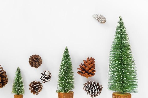 Fond de noël et du nouvel an. arbre de noël et des pommes de pin sur du papier blanc.