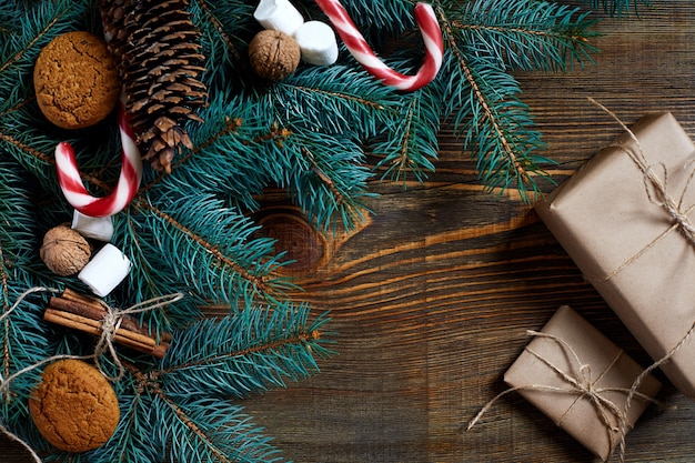 Fond de noël ou du nouvel an avec des biscuits épices noix de cannelle et branche de sapin sur bois foncé ...