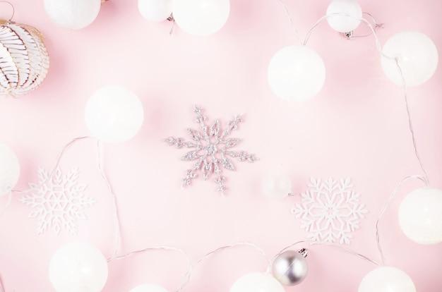 Fond de noël ou du nouvel an. boules blanches et argentées, flocons de neige décoratifs et guirlande lumineuse