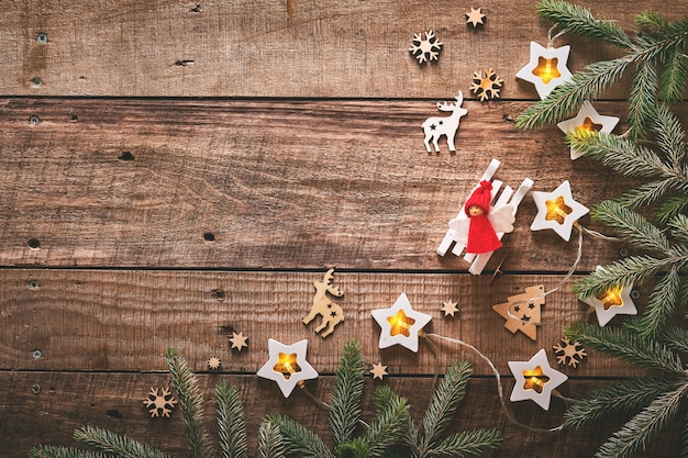Fond de noël ou du nouvel an avec des branches de sapin, des guirlandes, des boules de noël, une boîte-cadeau, des flocons de neige en bois et des étoiles sur fond en bois foncé. place pour votre texte