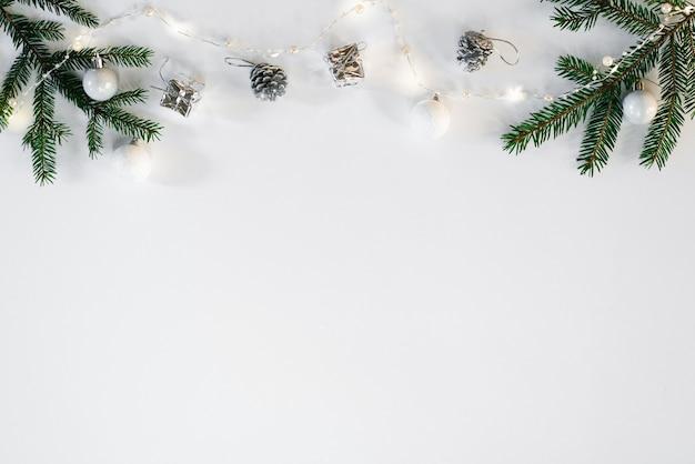 Fond de noël ou du nouvel an. composition de décorations de noël et de branches de sapin sur blanc. mise à plat