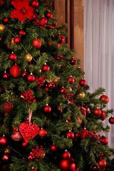 Le fond de noël ou du nouvel an est composé de grosses boules rouges sur des branches à l'intérieur du salon. intérieur de maison pour la célébration du nouvel an. cadeaux du nouvel an. contexte pour le site web. espace de copie