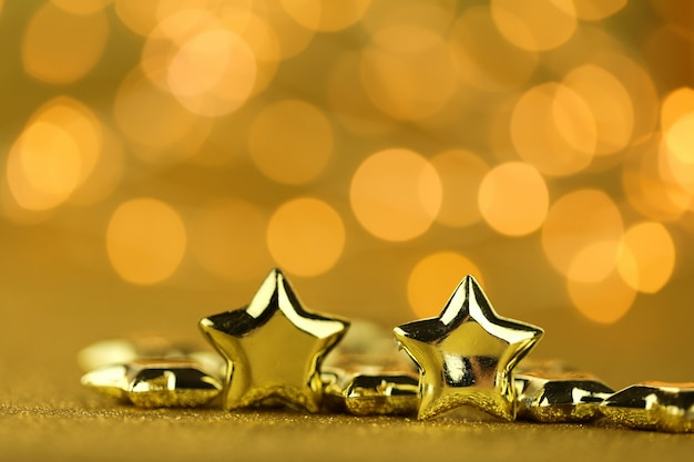 Fond de noël et du nouvel an. étoiles dorées gros plan sur un fond de paillettes d'or avec bokeh jaune.