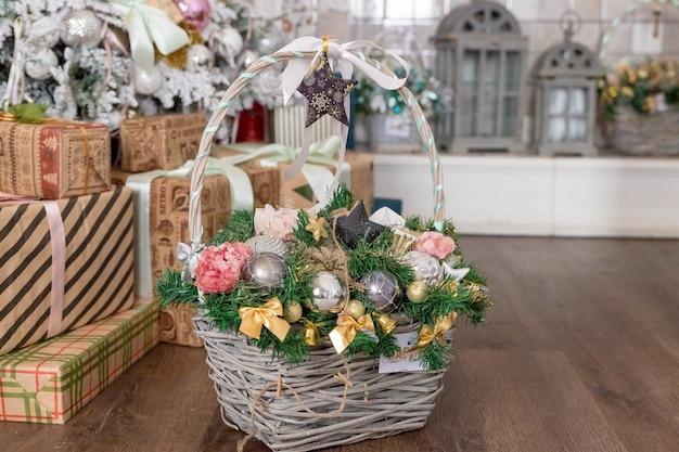 Fond de noël ou du nouvel an: panier avec des jouets en verre coloré et boules, décoration et cadeaux sur fond en bois près de sapin de noël. joyeuses fêtes.