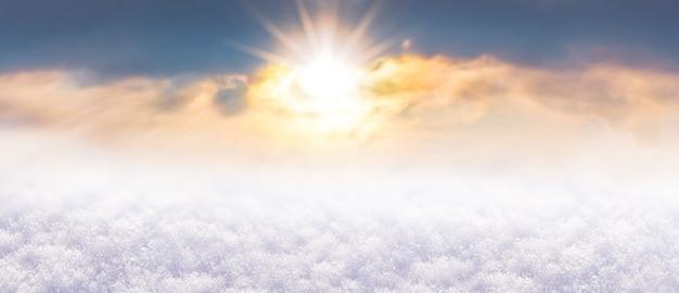 Fond de noël et du nouvel an avec un soleil brillant du soir sur la couverture de neige