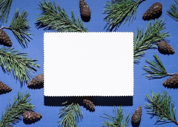 Fond de noël avec du papier à lettres sur bleu. décor de branches et de pommes de pin