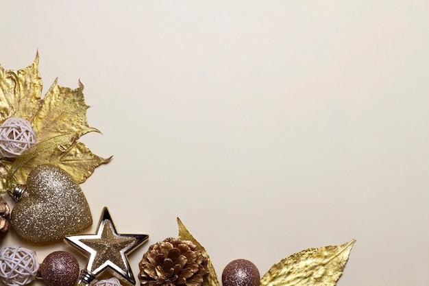 Fond de noël élégant avec des jouets dorés, des feuilles, des étoiles et des ballons sur un fond beige.