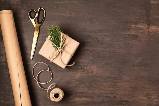 Fond de noël avec emballage de cadeaux faits à la main, présente sur table en bois rustique. emballage de bricolage de noël.