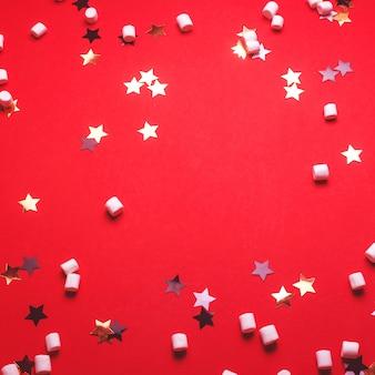 Fond de noël avec des étoiles et des guimauves sur rouge.