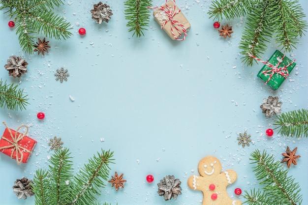 Fond de noël fait de branches de sapin, décorations, baies, pain d'épice sur fond bleu