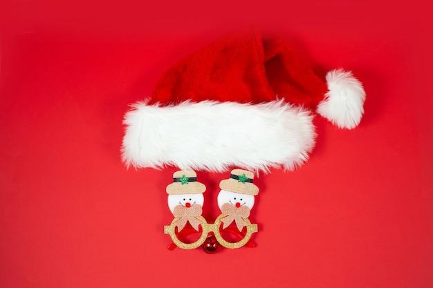 Fond de noël festif avec chapeau de noël et lunettes drôles sur fond rouge. nouveau concept de noël normal.