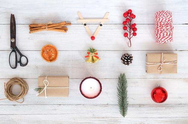 Fond de noël fond décoratif et boîtes à cadeaux sur panneau en bois blanc. création d'une disposition plate et d'une composition supérieure