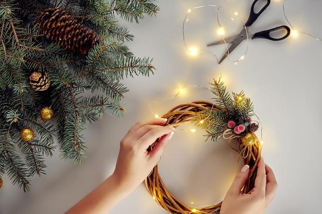 Fond de noël avec guirlande de décorations et pommes de pin créant une couronne faite d'arbre de noël ...
