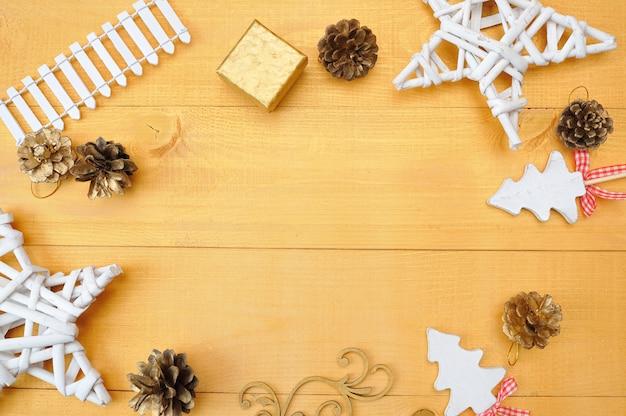 Fond de noël kraft feuille de papier avec la place pour votre texte et blanc étoile de sapin de noël et cône sur un fond en bois doré.