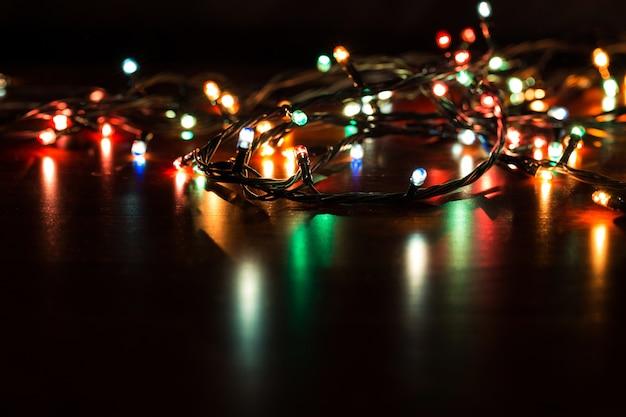 Fond de noël avec des lumières. lumières de noël colorées rougeoyantes sur fond noir.