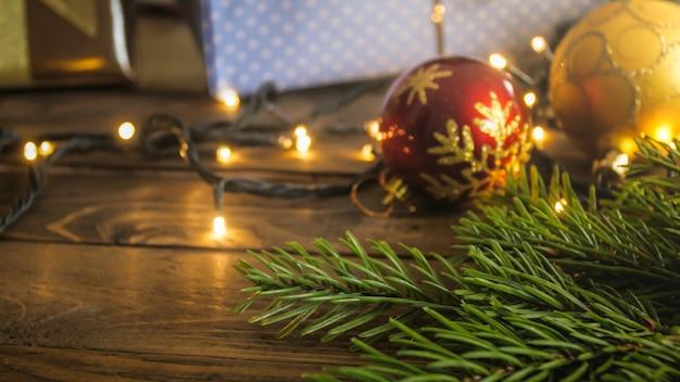 Fond de noël avec des lumières rougeoyantes, des boules et une couronne sur la table