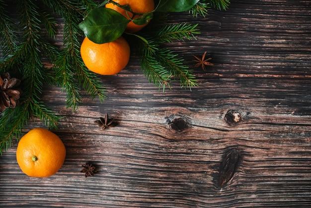 Fond de noël avec des mandarines, des branches de sapin et de l'anis étoilé