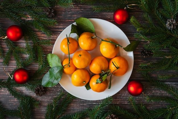 Fond de noël avec des mandarines, des branches de sapin, des boules rouges.