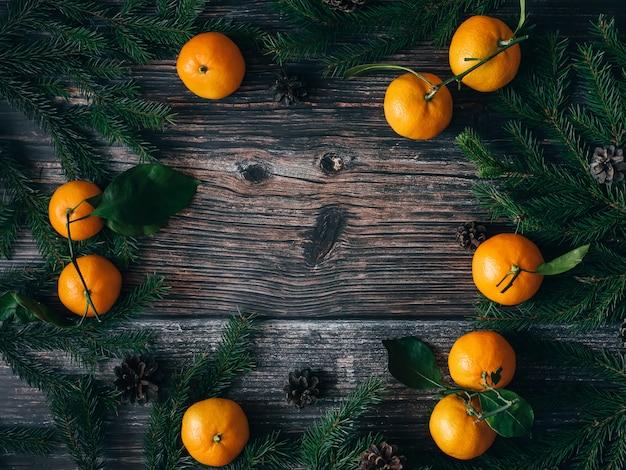 Fond de noël avec des mandarines, des branches de sapin et des pommes de pin. cadre de vacances d'hiver