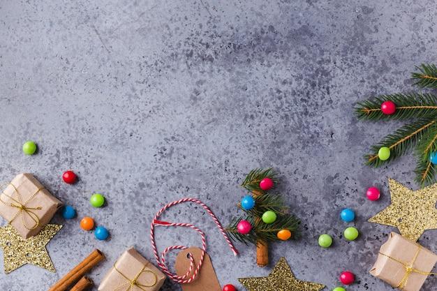 Fond de noël avec mini sapin de noël, coffrets cadeaux, décor festif, sapin, bonbons, bâtons de cannelle