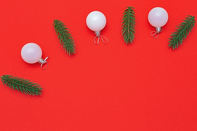 Fond de noël minimal avec des boules de verre blanc et des brindilles de sapin sur une surface de couleur rouge