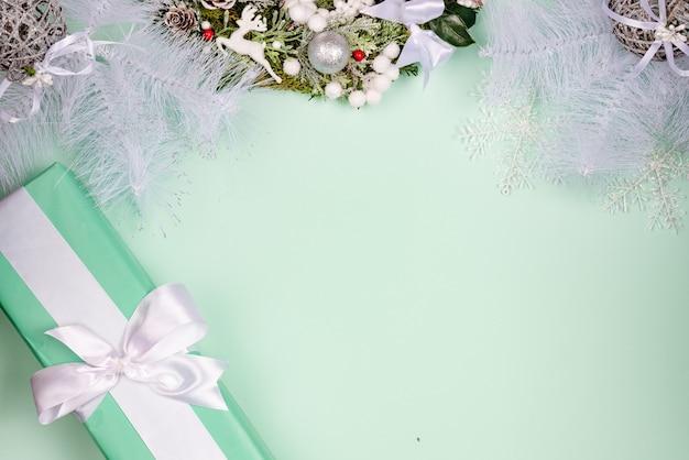 Fond de noël minimaliste avec des branches de sapin et des décorations, coffret bleu