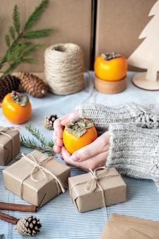 Fond de noël naturel, coffrets cadeaux artisanaux, cônes, arbre de noël sur la table, gros plan, style rétro. une fille en pull emballe des cadeaux. l'atmosphère joyeuse des vacances.